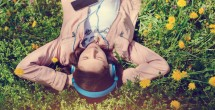 serene girl lying in a meadow listening to music on headphones