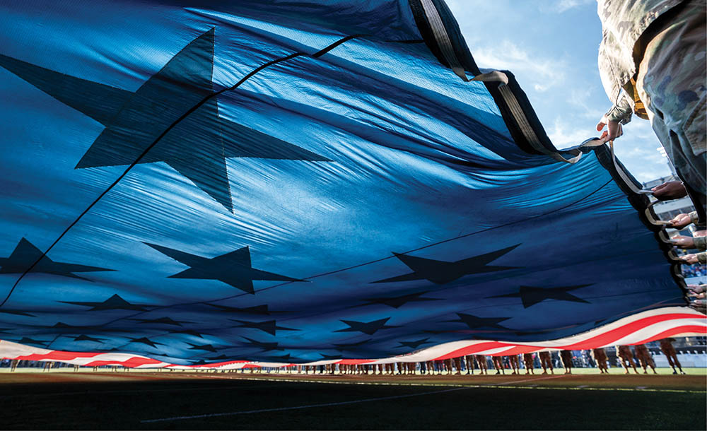 Close-up photo of giant U.S. flag being unfurled on the football field