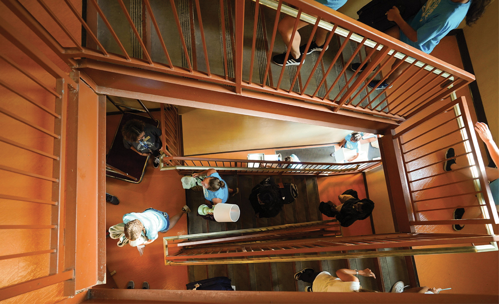 overhead view of a stairwell with students carrying their belongings