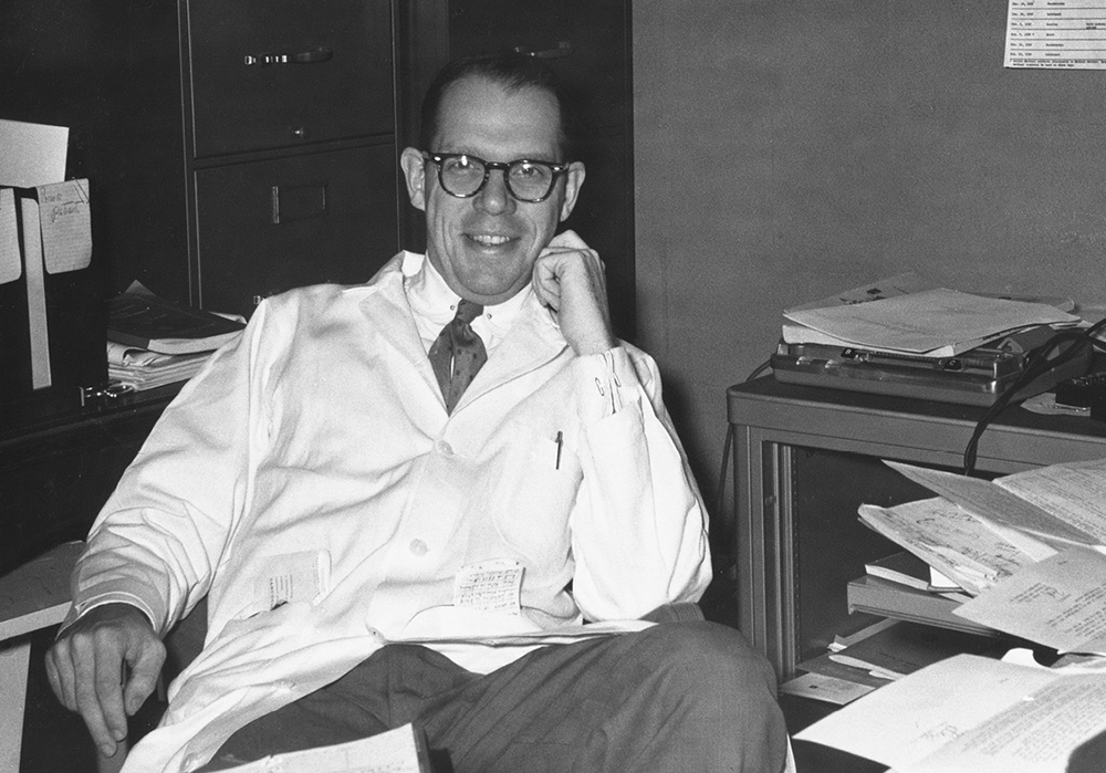 Black and white photo of a grinning Dr. Blair Batson in his messy office