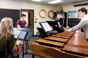 Blair student Chris Bell rehearsing his composition with chatterbird chamber ensemble musicians playing flute, marimba and singing.