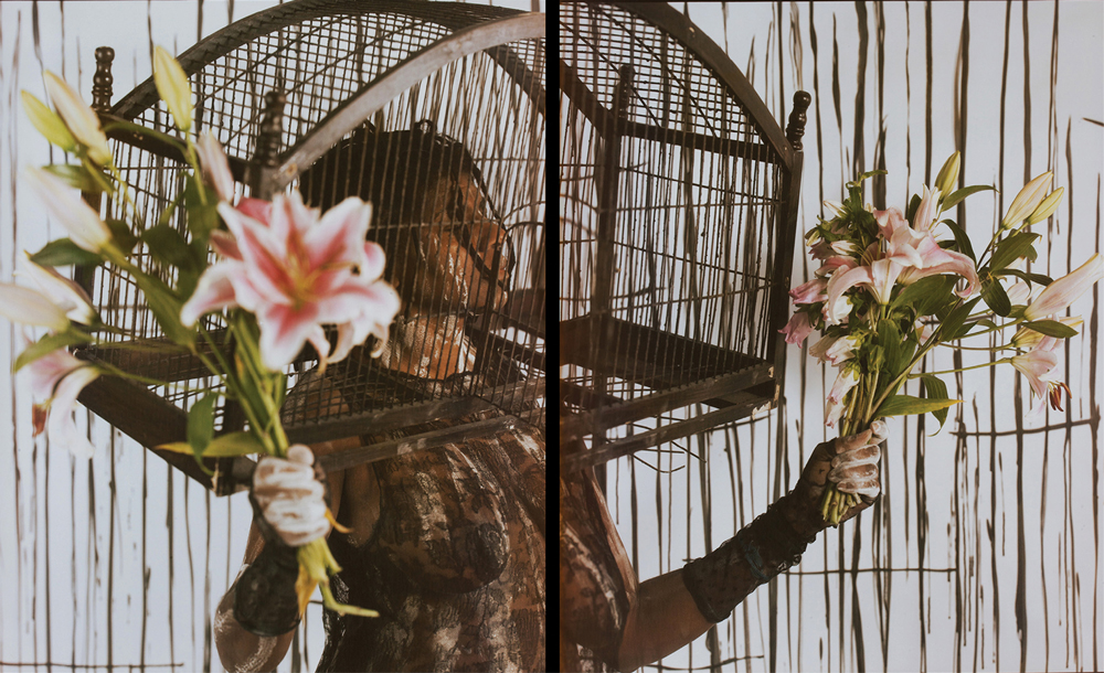 photo of Campos-Pons with her head in a birdcage and flower bouquets in each hand