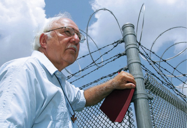 Color portrait of Rev. Don Beisswenger in front of prison fence