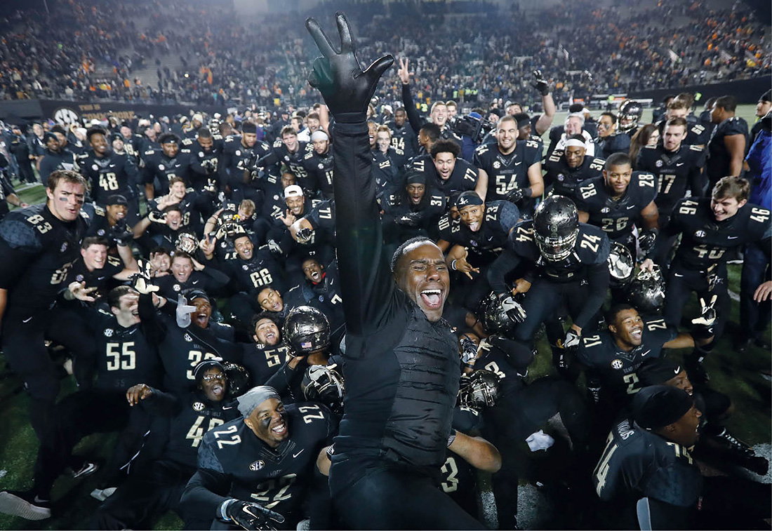 Coach Mason and the team celebrate their 45–34 victory over Tennessee last November. (JOHN RUSSELL)