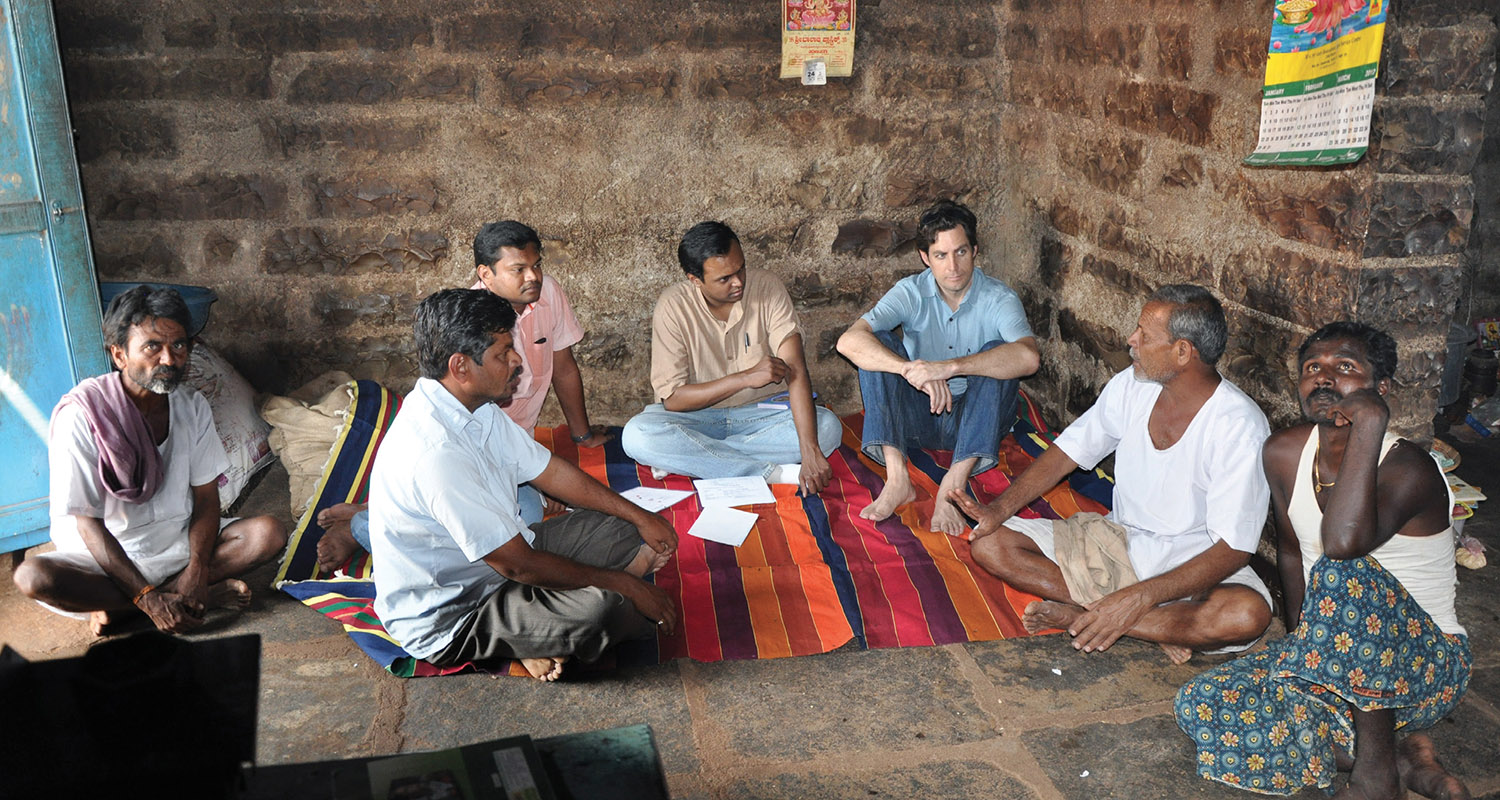 Michael MacHarg (third from right), senior director of social ventures for Mercy Corps and co-founder of Simpa Energy, interviews a homeowner in a village without electricity in rural Karnataka, India, with two of his Simpa colleagues. (COURTESY MICHAEL MACHARG)