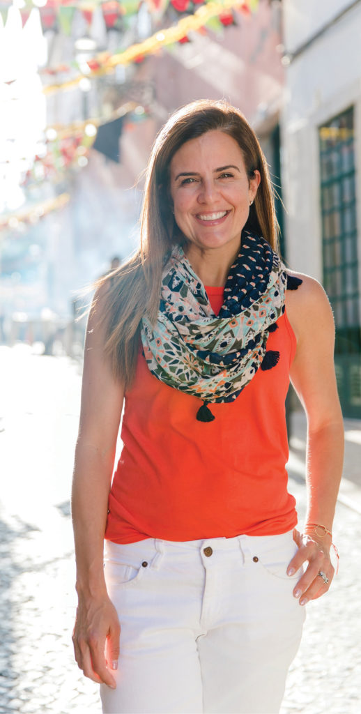 Nicole Feliciano, wearing orange blouse and white pants on a colorful street