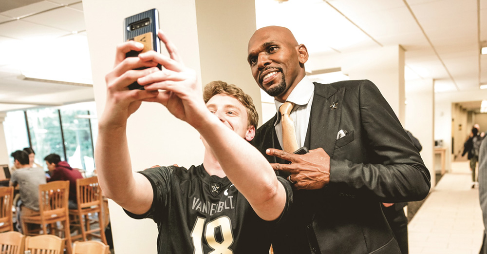 photo of Jerry Stackhouse taking a selfie with a student