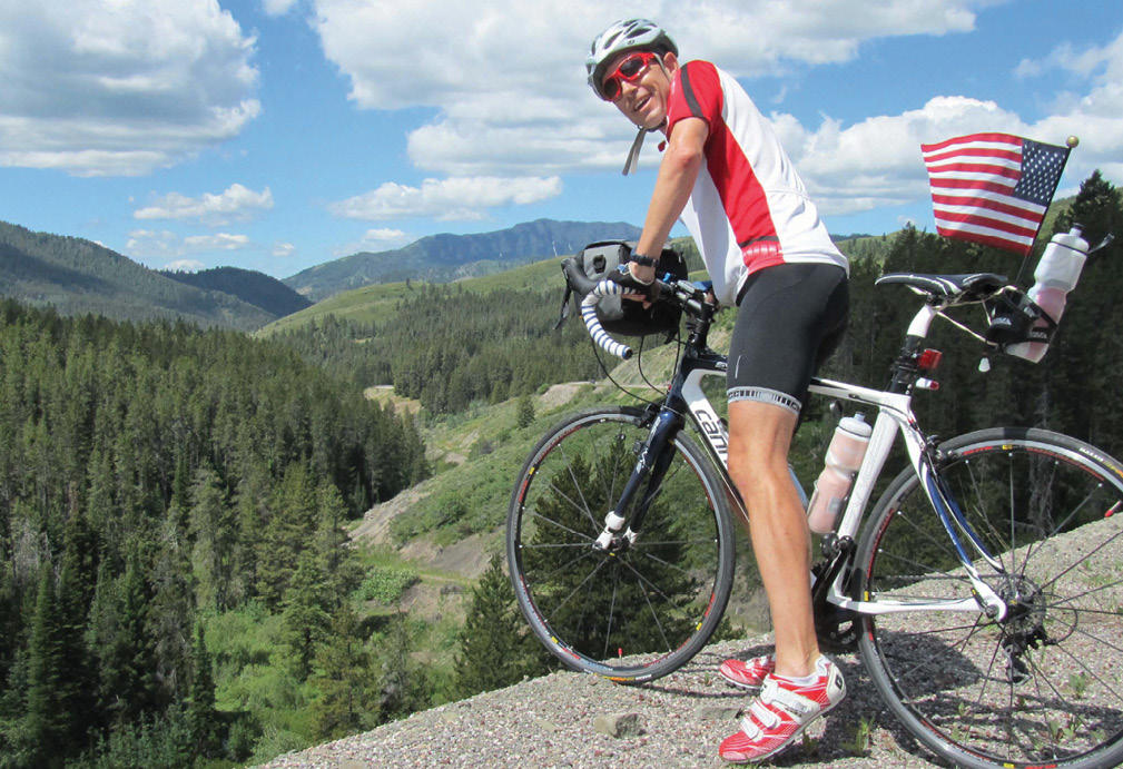 Todd Miller on a bicycle in Wyoming surrounded by hills and mountains