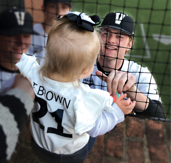 photo of Tyler Brown visiting with Bella in the dugout