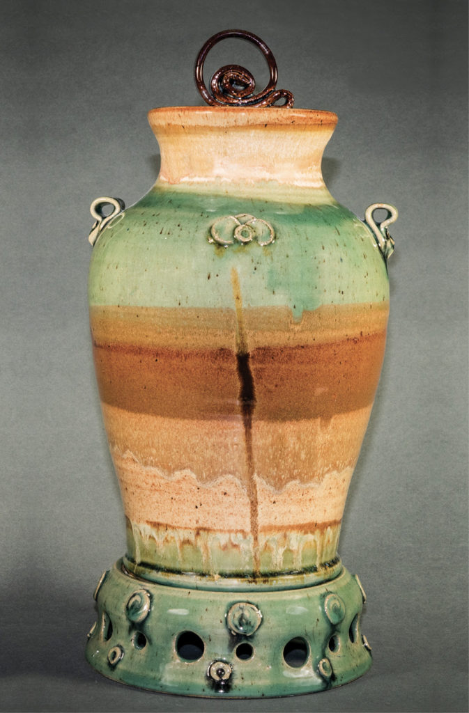 This tall, earth-tone glazed vase is one of Susan DeMay's classroom demonstration pieces, 17x8x8 inches, completed in stages throughout a semester for an assignment involving numerous objectives for honing pottery wheelwork techniques. Photo by Bill Luton
