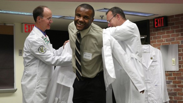 At last week's ceremony, first-year School of Medicine student Chike Abana, center, gets a little help donning his white coat from Scott Rodgers, M.D., left, and Jeff Balser, M.D., Ph.D. (photo by Anne Rayner)